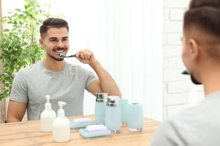 Young man brushing teeth near mirror in bathroom at home