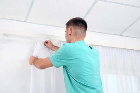 Man hanging window curtain indoors. Interior decor element