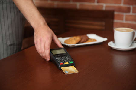 Waiter with terminal for contactless payment in cafe, closeup