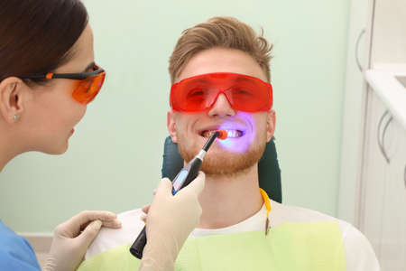 Professional dentist working with patient in modern clinic. Teeth whitening