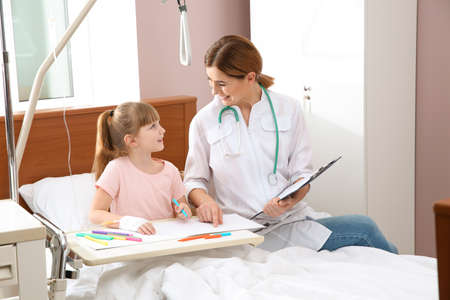 Little child with intravenous drip drawing in hospital bed during doctor's visit