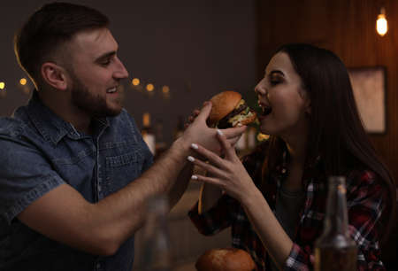 Young couple having lunch in burger restaurant