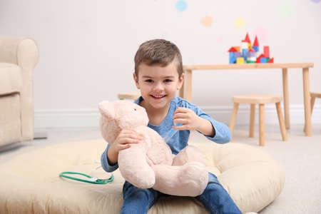 Bambino carino che gioca al dottore con un peluche sul pavimento in ospedale Archivio Fotografico