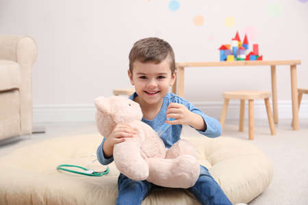 Cute child playing doctor with stuffed toy on floor in hospital Imagens