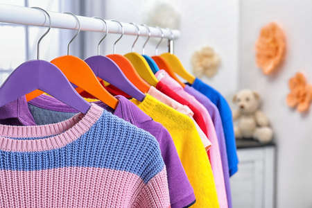 Colorful children's clothes hanging on wardrobe rack indoors, closeup