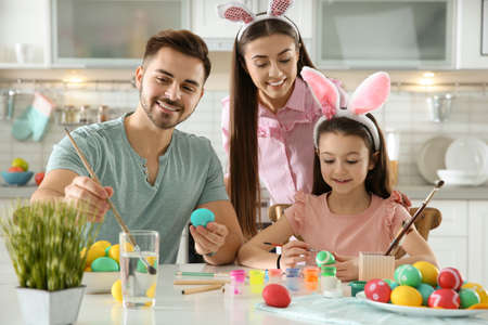 Father, mother and daughter painting Easter eggs in kitchen Stock Photo - 120061062