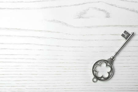 Old vintage key on wooden background, top view with space for text 免版税图像