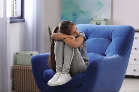 Depressed preteen girl sitting in armchair at home