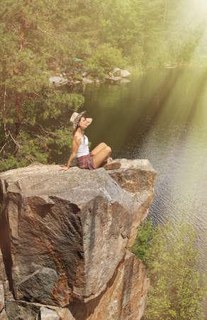 Young woman on rocky mountain near lake. Zen, balance, harmony
