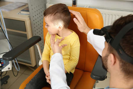 Professional otolaryngologist examining little boy in clinic. Hearing disorder