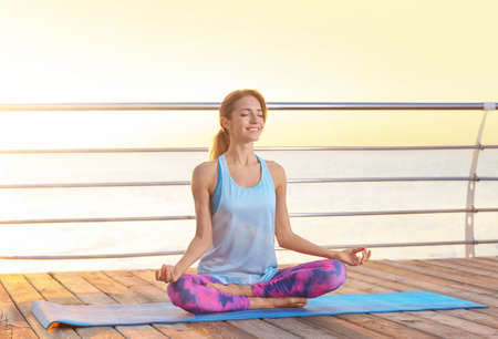 Young woman practicing zen yoga on pier