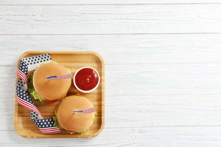 Tasty burgers, sauce and USA flag ribbon on wooden background, top view with space for text. Traditional American food