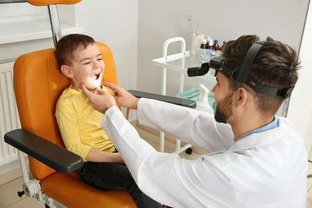 Professional otolaryngologist examining little boy in clinic