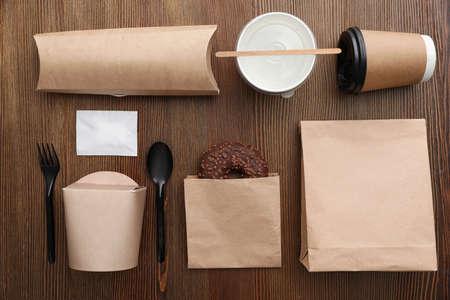 Composición laicos plana con bolsas de papel y diferentes artículos para llevar sobre fondo de madera. Espacio para el diseño