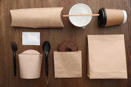 Flat lay composition with paper bags and different takeaway items on wooden background. Space for design