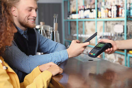 Clients using smartphone and credit card machine for non cash payment in cafe