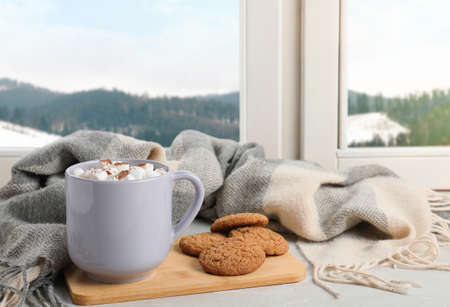 Composition with cup of hot winter drink and cookies on windowsill