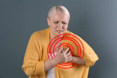 Mature woman suffering from heart attack on color background Imagens