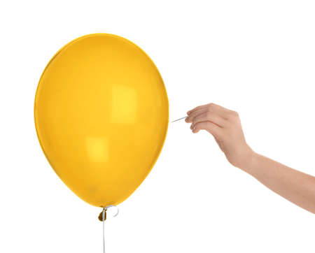 Woman piercing gold balloon on white background, closeup