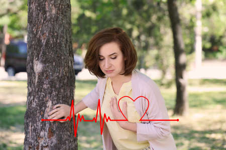 Mature woman suffering from heart attack outdoors