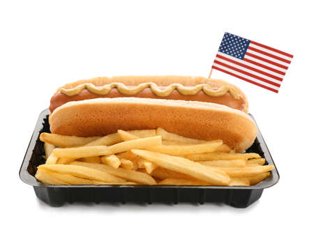 Hot dog with USA flag and French fries in container on white background. Traditional American food