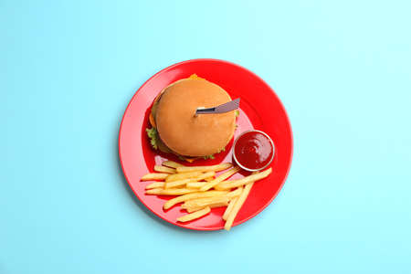 Plate with burger and French fries on color background, top view. Traditional American food Stock Photo