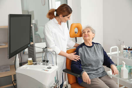 Senior woman visiting professional otolaryngologist in clinic. Hearing disorder