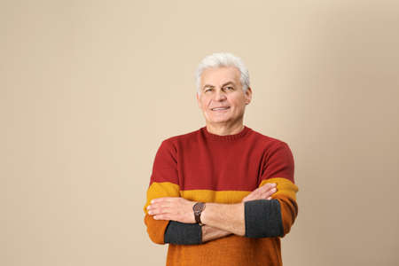 Portrait of handsome mature man on color background. Space for text