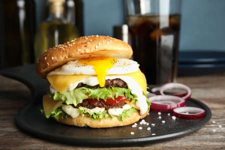 Tasty burger with fried egg on tray against blurred background Stock fotó