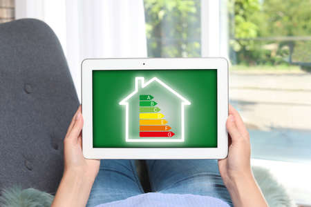 Woman using tablet with icon of energy efficiency on screen, closeup