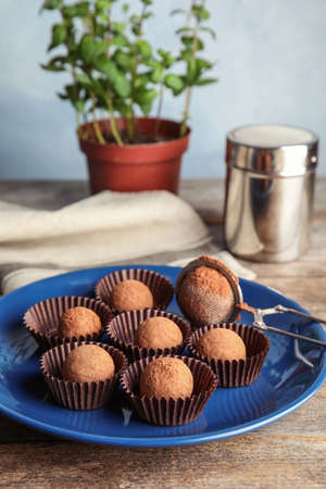 Plate with chocolate truffles on wooden table Stock Photo