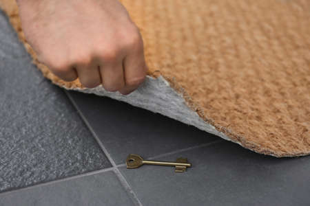 Man lifting door mat and finding hidden key, closeup view