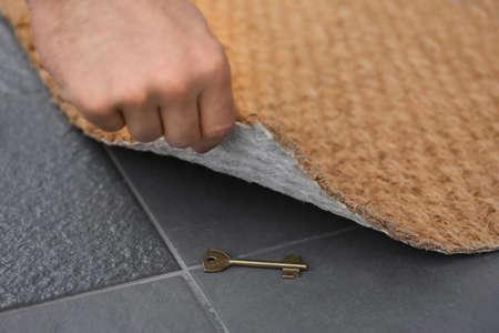Man lifting door mat and finding hidden key, closeup view