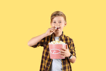 Cute boy with popcorn bucket on color background