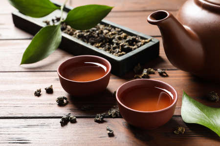 Cups and teapot of Tie Guan Yin oolong on wooden table Imagens