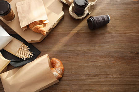 Paper bags with pastry and takeaway food on wooden table, top view. Space for text