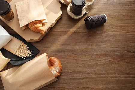 Papiertüten mit Gebäck und Speisen zum Mitnehmen auf Holztisch, Ansicht von oben. Platz für Text Standard-Bild