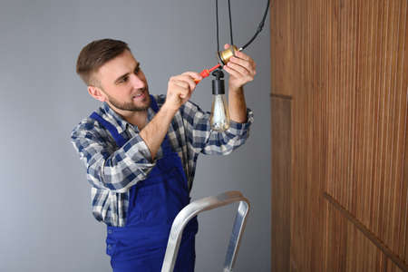 Electrician with screwdriver repairing ceiling lamp indoors. Space for text