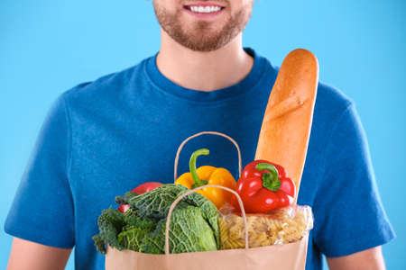 Delivery man holding paper bag with food products on color background, closeup Stock Photo