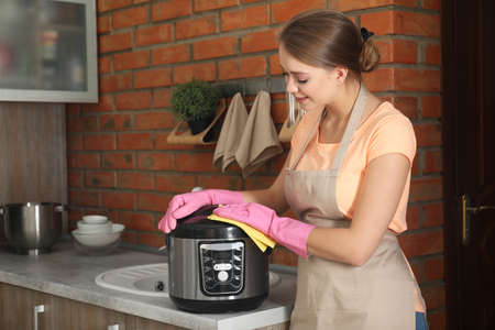 Young woman cleaning modern multi cooker in kitchen