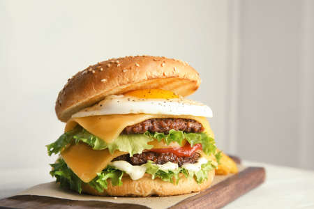Tasty burger with fried egg on board against light background