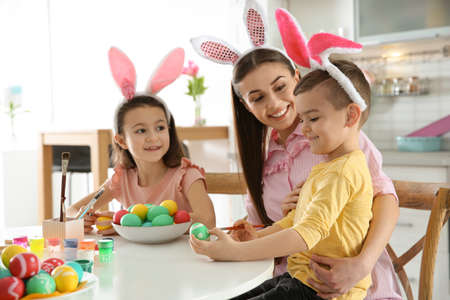 Mother and her children with bunny ears headbands painting Easter eggs in kitchen