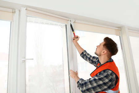 Construction worker installing plastic window in house Stock Photo