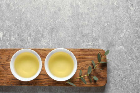 Stand with cups of freshly brewed oolong tea on grey background, top view with space for text