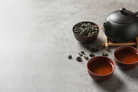 Teapot, cups of Tie Guan Yin oolong and tea leaves on table. Space for text