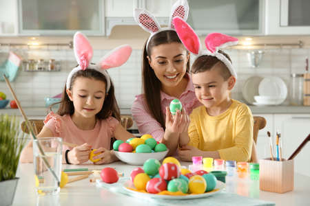 Mother and her children with bunny ears headbands painting Easter eggs in kitchen Stock Photo - 120079070