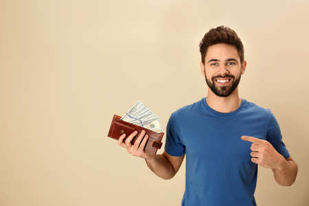 Happy young man with wallet full of money on color background. Space for text