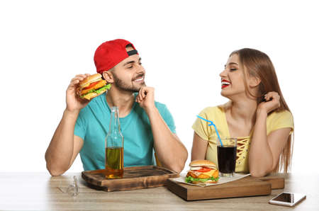 Happy couple having lunch with burgers at table on white background Banco de Imagens