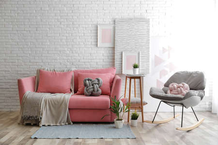 Stylish living room interior with sofa and rocking armchair near brick wall. Space for text Banco de Imagens