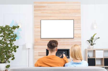 Par viendo la televisión en el sofá en el salón con chimenea decorativa Foto de archivo